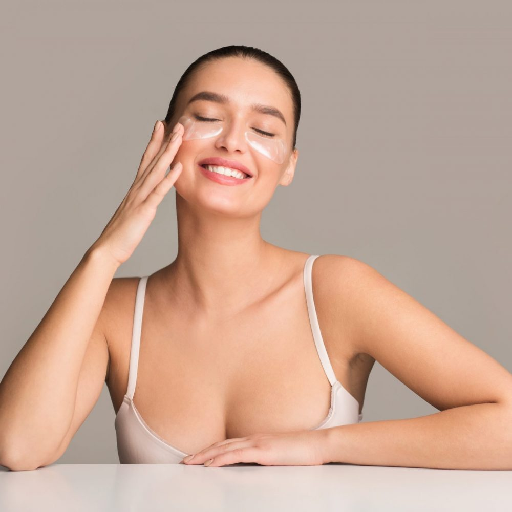 Happy woman with collagen pads under eyes over grey studio background