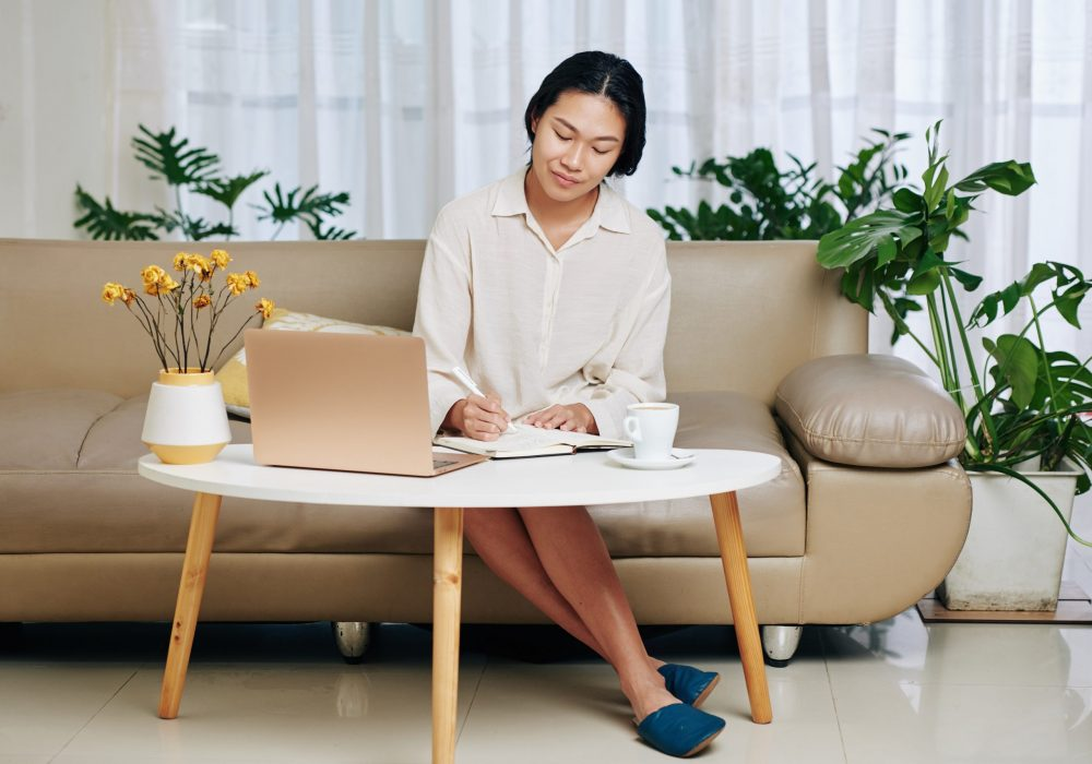 Pretty young Asian woman doing homework at coffee table at home, filling planner and sending e-mails